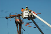 Two men working on powerlines from a cherry pikcer